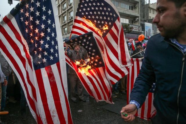 Des manifestants brûlent des drapeaux américains lors d'une... (PHOTO REUTERS)