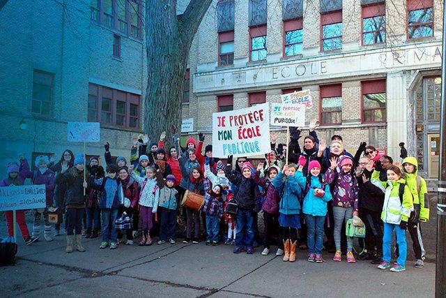 Des enfants qui brandissent des pancartes. Des parents et des enseignants qui...