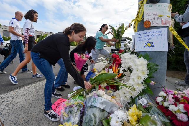 Des résidants de Poway ont déposé des fleurs... (PHOTO DENIS POROY, ASSOCIATED PRESS)