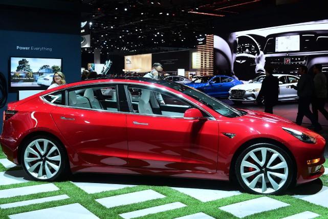 Cette Tesla Model 3 Standard rouge comme le... (PHOTO FREDERIC J. BROWN, AFP)