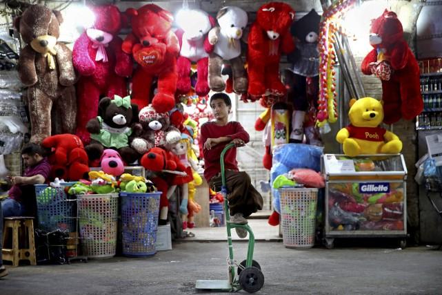Un jeune marchand de bazar pose devant son... (PHOTO AP)