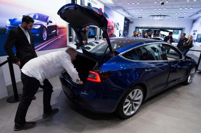 Des acheteurs potentiels inspectent le coffre d'un Model... (PHOTO JOSEP LAGO, AFP)