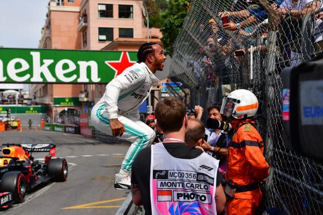 Lewis Hamilton a sauté sur la clôture pour... (PHOTO ANDREJ ISAKOVIC, AFP)