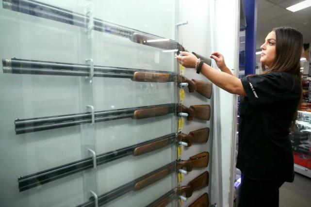 Une employée manipule une arme à feu dansunmagasin... (PHOTO RICK RYCROFT, ARCHIVES ASSOCIATED PRESS)