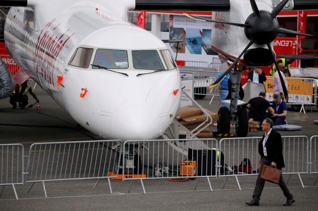 Un homme passe devant un appareil de BombardierQ400... (PHOTO PASCAL ROSSIGNOL, REUTERS)
