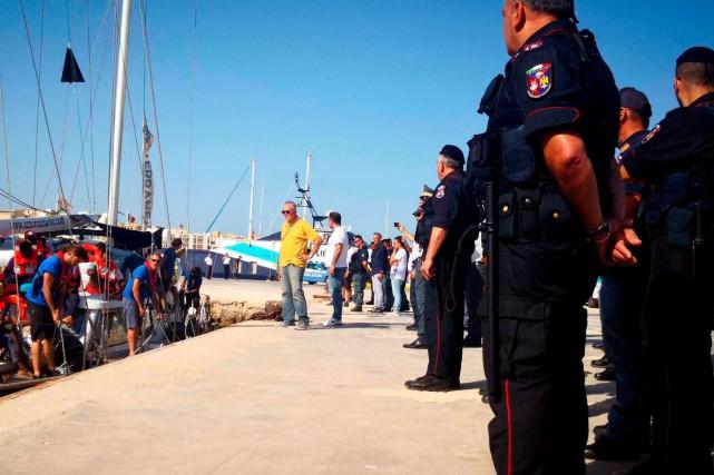 Des policiers italiens supervisent le débarquement de migrants... (PHOTO AP)