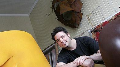 Stéphane Langlois appuyé sur ses sculptures de bois....