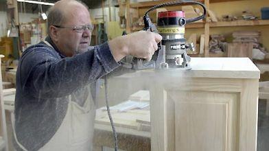 Un menuisier travaille sur une armoire de bois...