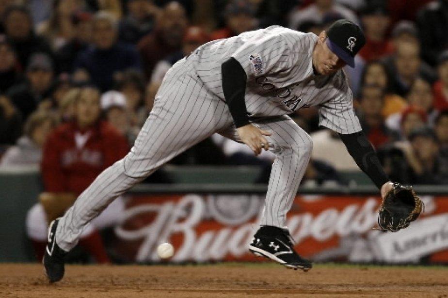 Le joueur de troisième but des Rockies, Garrett Atkins, se penche pour saisir un roulant. | 1 mars 2011