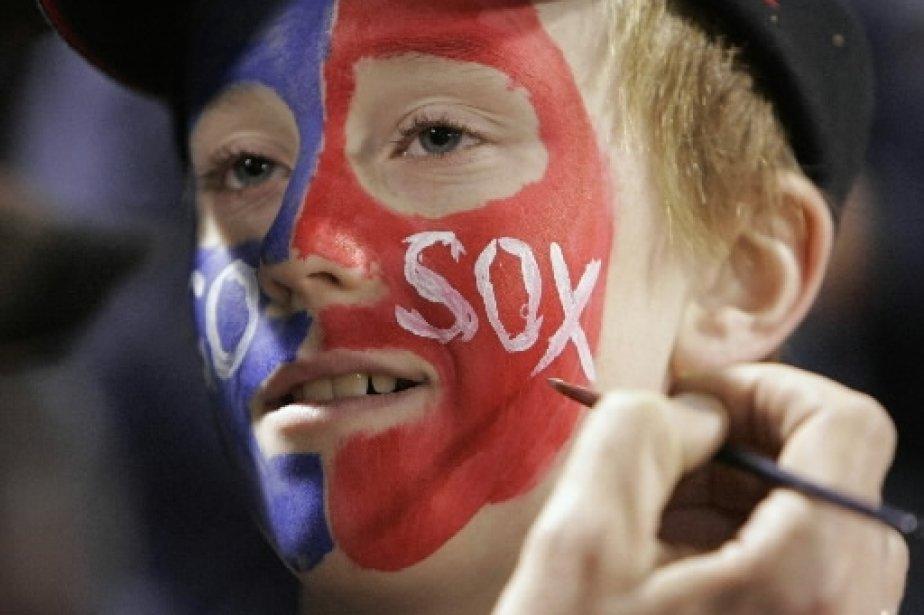 Ce jeune fan des Red Sox se fait peindre le visage aux couleurs de son équipe favorite avant le match. | 1 mars 2011
