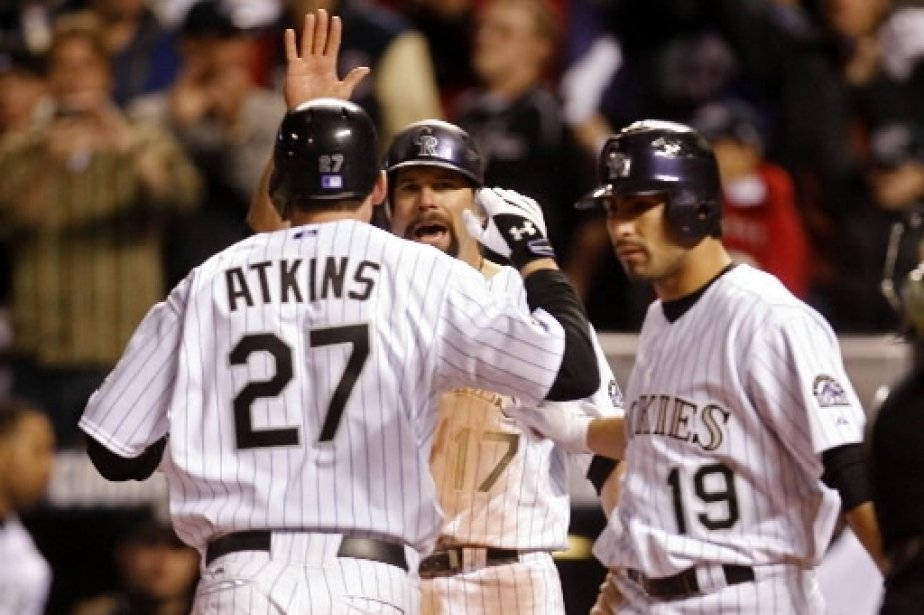 Garrett Atkins est félicité par Todd Helton, et Ryan Spilborghs après son circuit qui ramène les Rockies à un point des Red Sox. | 1 mars 2011