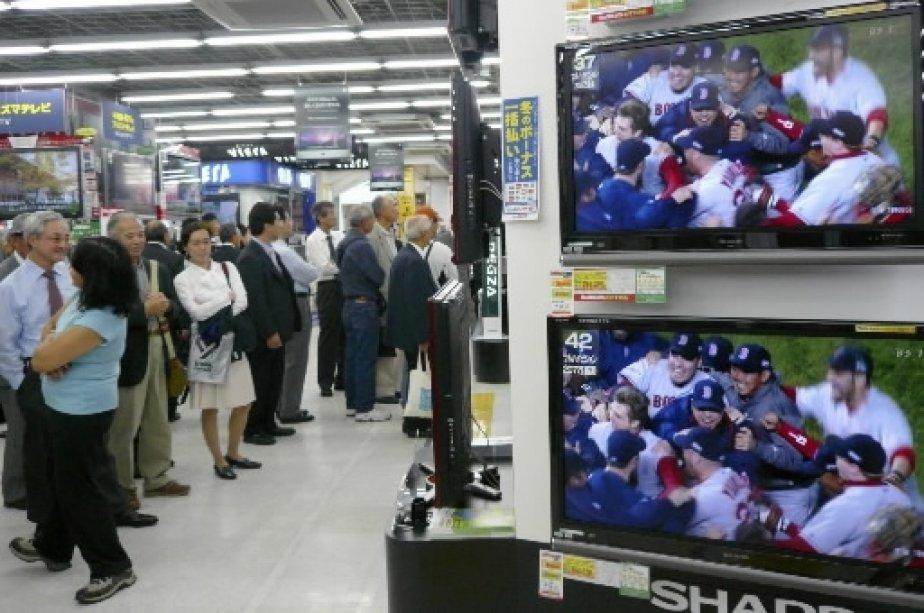 Des Japonais regardent les célébrations depuis un magasin d\\'électronique. | 1 mars 2011