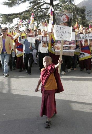 Un enfant moine tient une photo de personnes... (Photo AP)