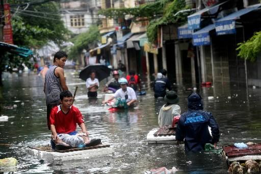 Des résidents d'Hanoï marchent dans les rues inondées.... (Photo: Bloomberg News)