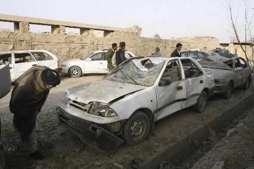 Un Afghan inspecte une voiture endommager par l'explosion.... (Photo: AP)