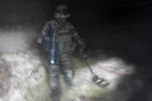 Avec un détecteur de métal, un soldat français... (Photo: AFP)