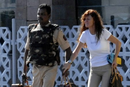 Un policier indien aide une cliente à quitter... (Photo: Reuters)