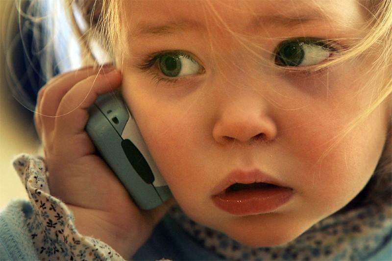 Une petite fille parle au cellulaire... (AFP)