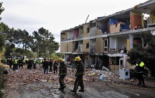 Des pompiers inspectent le site de l'explosion.... (Photo: AP)
