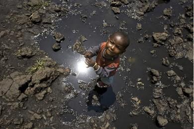Un enfant joue dans une flaque de boue... (Photo: Reuters)