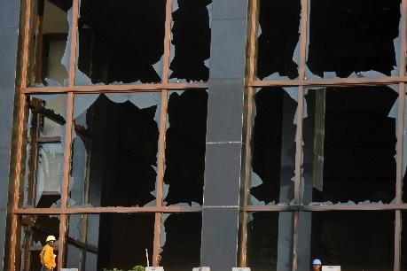 Un travailleur se tient devant des fenêtres fracassées... (Photo: Reuters)
