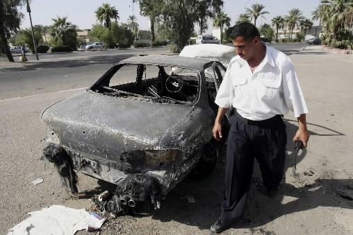 Un policier iraquien inspecte une voiture incendiée par... (Photo: AP)