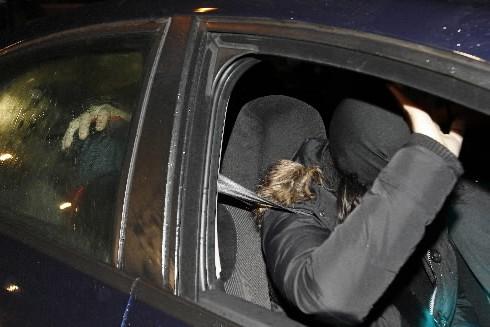 Un policier abaisse la tête du présumé chef... (Photo: Reuters)
