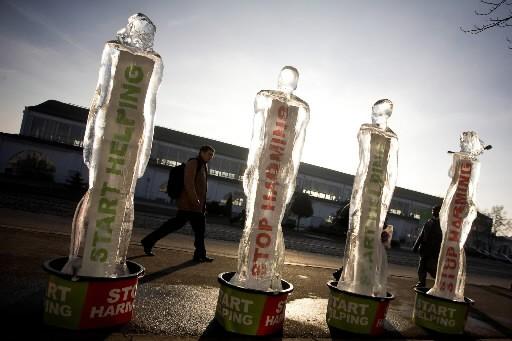 Des délégués marchent près de sculptures de glace... (Photo: AFP)