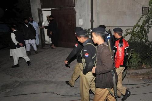 Des policiers pakistanais marchent devant la maison de... (Photo: AFP)