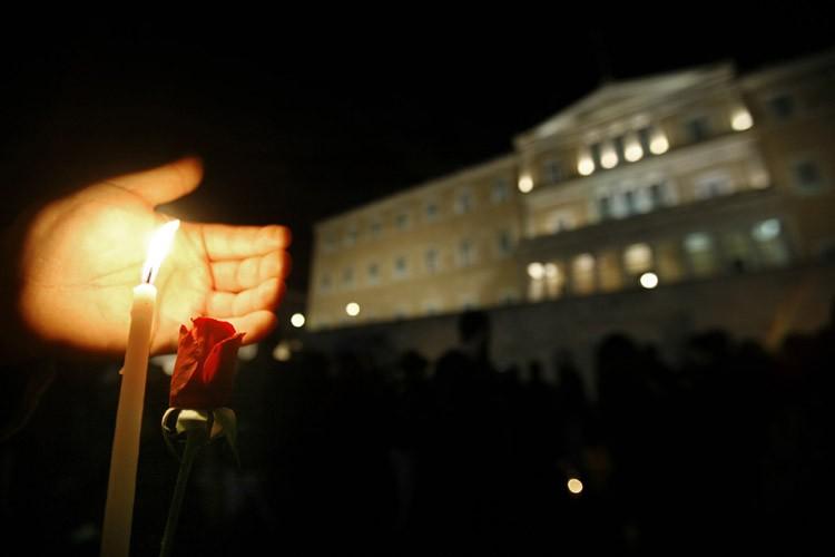 Un jeune manifestant tient une chandelle et une... (Photo: AFP)