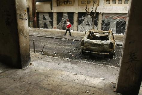 Une femme passe près d'une voiture incendiée à... (Photo: Reuters)
