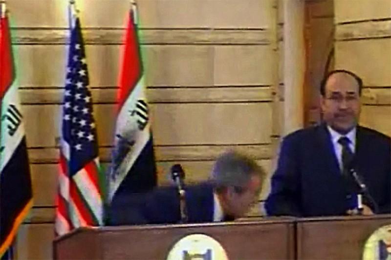 George Bush se penche pour éviter un soulier... (AFP)