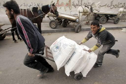 Des Palestiniens transportent des sacs de farine reçus... (Photo: Reuters)