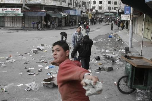 Un Palestinien lance des roches aux soldats israéliens... (Photo: AP)