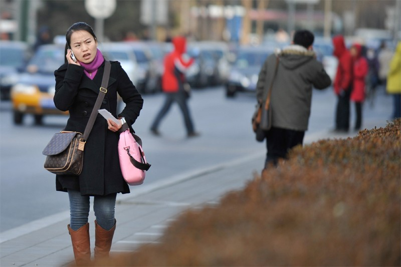 Une femme parle au cellulaire à Pékin... (Bloomberg)