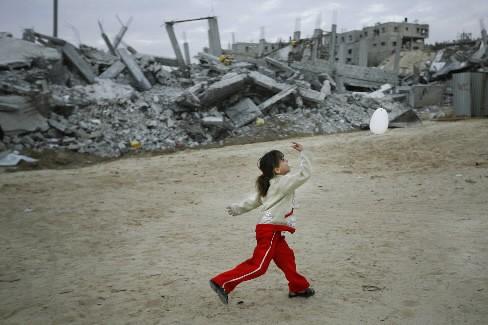 Une jeune fille joue avec un ballon devant... (Photo: AP)
