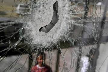 Une fillette regarde une fenêtre brisée par une... (Photo: Reuters)