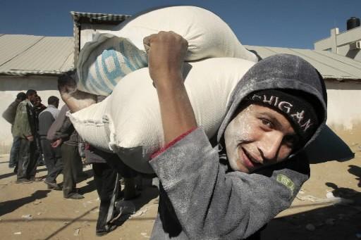 Un jeune homme transporte un sac de farine... (Photo: Reuters)