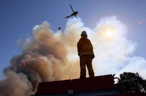 Un pompier observait hier un hélicoptère larguer une... (Photo: AFP)