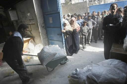 Un employé transporte des sacs de nourriture alors... (Photo: AFP)