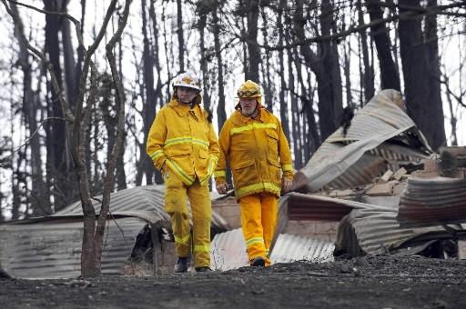 Deux pompiers examinent les dommages causés par les... (Photo: AP)