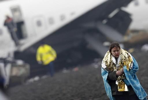 Une passagère s'éloigne de la carcasse de l'avion.... (Photo: Reuters)