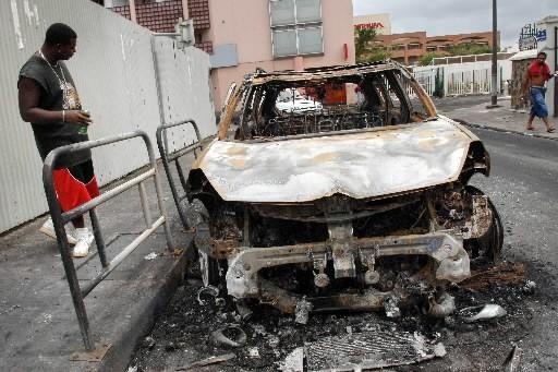 Un homme examine une voiture brûlée à Fort-de-France... (Photo: AFP)