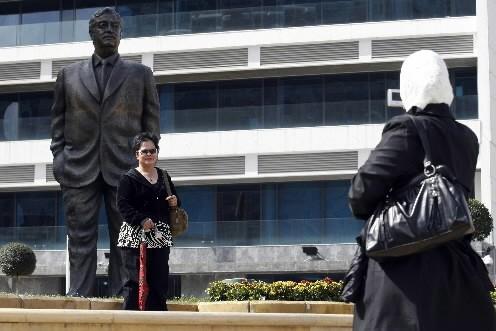 Une femme pose près de la statue de... (Photo: AFP)