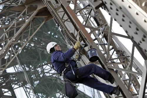 Un homme repeint une partie de la Tour... (Photo: AP)