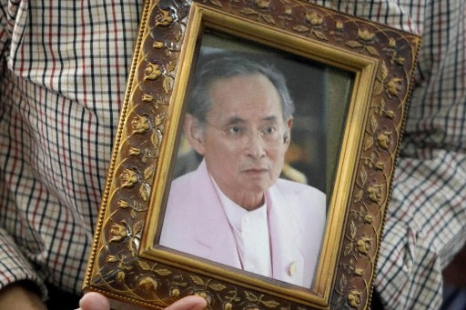 Une femme tient une photo de Bhumibol Adulyadej.... (Photo: AFP)