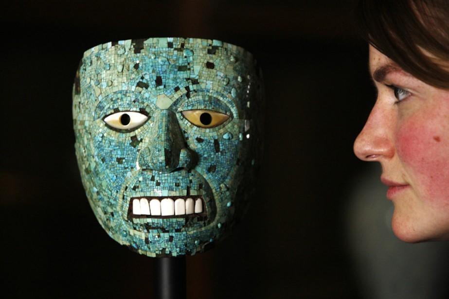 Une jeune femme admire un masque de l'empereur... (Photo: AP)