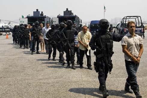 Les personnes interpelées sont sous escorte policière.... (Photo AFP/Alfredo Estrella)