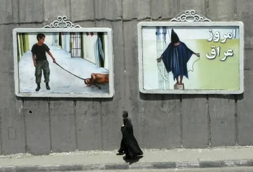 Une femme passe près d'affiches de la prison... (Photo: AFP)