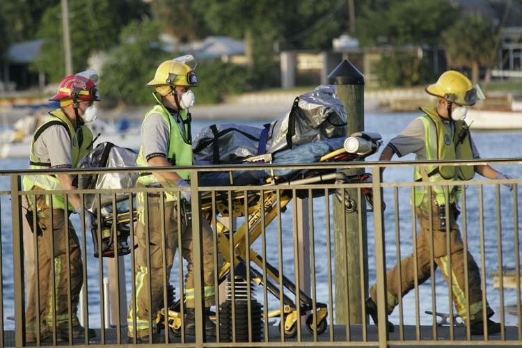 Des pompiers transportent un cadavre débarqué d'un vaisseau... (Photo: AP)